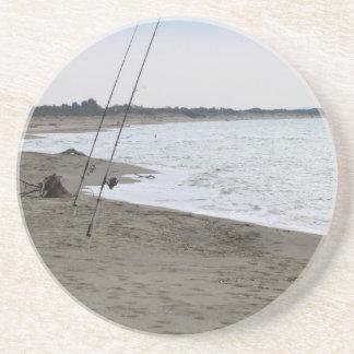 Angelruten auf einem sandigen Strand am Sandstein Untersetzer