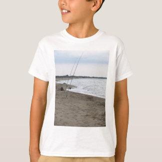 Angelruten auf einem sandigen Strand am T-Shirt