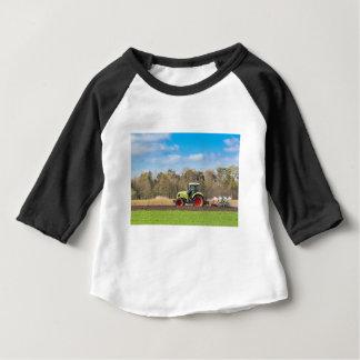 Bauer auf dem Traktor, der sandigen Boden im Baby T-shirt