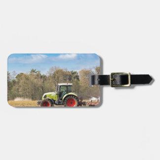 Bauer auf dem Traktor, der sandigen Boden im Kofferanhänger