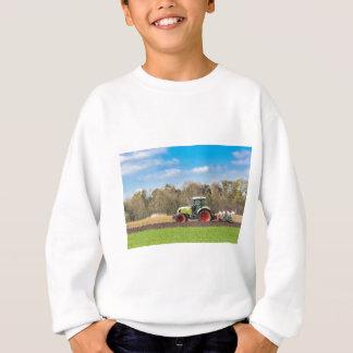 Bauer auf dem Traktor, der sandigen Boden im Sweatshirt