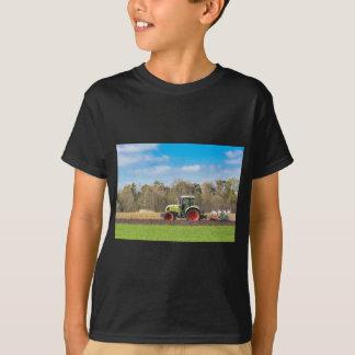 Bauer auf dem Traktor, der sandigen Boden im T-Shirt