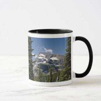 Bergspitze zwischen Bäumen unter einem blauen Tasse