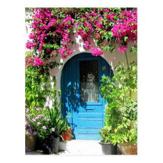 Blaue Tür gerahmt mit schönem Bouganvilla Postkarte