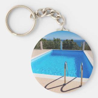 Blauer Swimmingpool mit Schritten in Meer Schlüsselanhänger