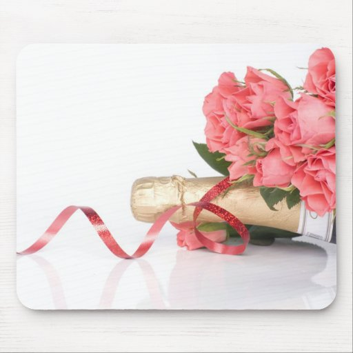 bottle of champagne and pink flowers tapis de souris