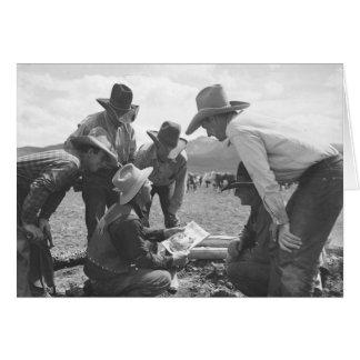 Cowboys, die eine Zeitschrift betrachten Karte