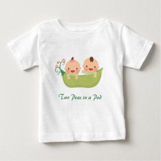Deux pois mignons dans des jumelles d'une fille de tshirt