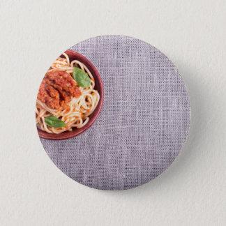 Draufsicht einer grauen Matte mit Spaghettis Runder Button 5,1 Cm