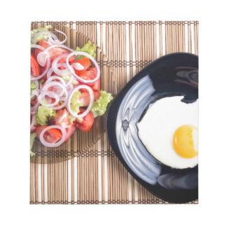 Draufsicht über ein Spiegelei und einen Salat der Notizblock