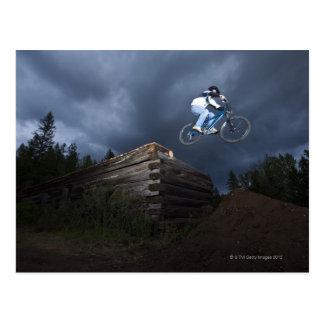 Ein Mountainbiker springt weg von einem Blockhaus Postkarte