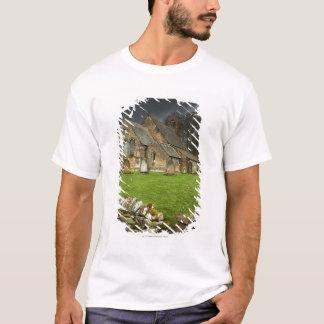 Eine alte Kirche unter einem dunklen Himmel T-Shirt