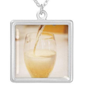Eine Champagnerglasflöte, die mit Gosset gefüllt Versilberte Kette