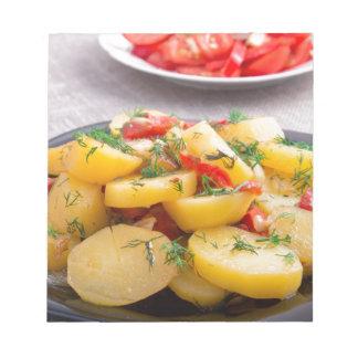 Eintopfgericht der Kartoffeln mit Zwiebel, grüner Notizblock