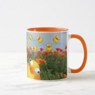 Enten, die in eine Wiese der Mohnblumen-Pflanzen Tasse