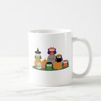 Eulen in Halloween-Kostümen, die auf Kürbis-Tasse Tasse