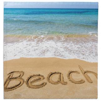 Fassen Sie den Strand ab, der in Sand in Stoffserviette