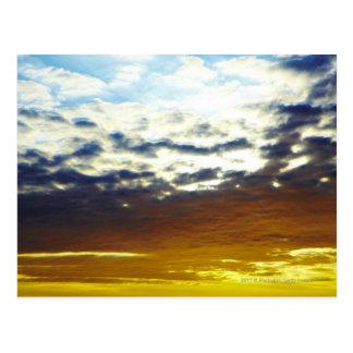 Gelber blauer schwermütiger Sonnenuntergang mit Postkarte