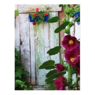 Griechische blaue Tür im Blumen-Garten in Postkarte