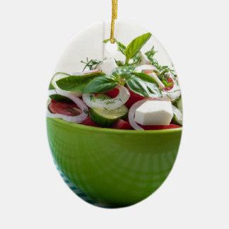 Grüne Schüssel mit Gemüsesalat auf Tischdecke Keramik Ornament