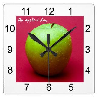 Grüner Apfel auf rotem Hintergrund Quadratische Wanduhr
