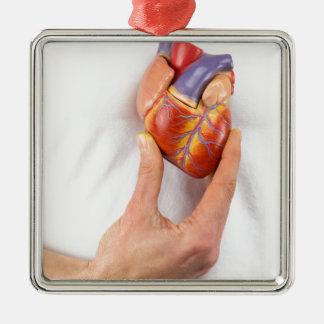 Hand, die vorbildliches Herz auf Kasten hält Silbernes Ornament