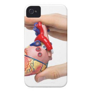 Hand hält vorbildliches menschliches Herz zwischen iPhone 4 Hülle