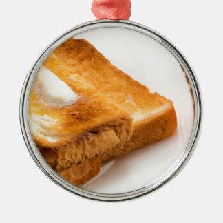 Heißer Toast mit Butter auf einer weißen Platte Rundes Silberfarbenes Ornament