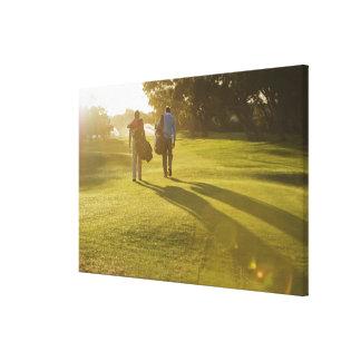 Hommes portant des sacs de golf sur le terrain de  toile tendue