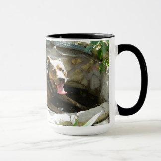 Hund, der in der Wasser-Tasse abkühlt Tasse