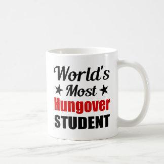 Hungover Studenten-lustiges Trinken der Welt der Kaffeetasse