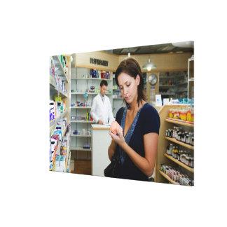 Jeune femme regardant la médecine dans la pharmaci toiles tendues