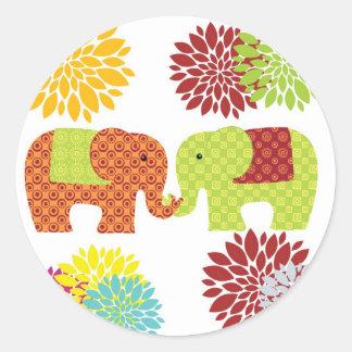 Jolis éléphants dans l'amour tenant des fleurs de adhésifs ronds