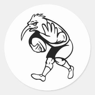 Joueur de rugby d'oiseau de kiwi avec la boule autocollant rond