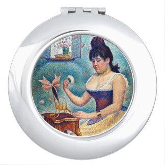 Junge Frau, die sich pulverisiert Taschenspiegel