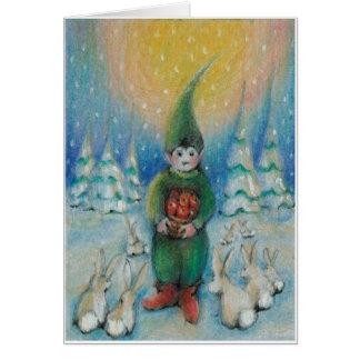 Junge tomte füttert Schneehäschen mit seinen Grußkarte