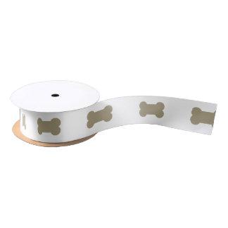 kakifarbige beige Hundeknochen auf hellem weißem Satinband