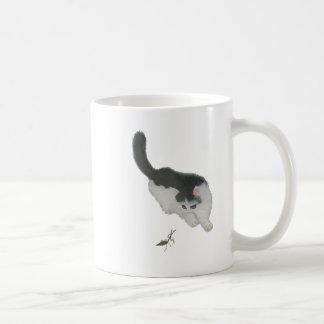 Katze, die Kricket jagt Kaffeetasse