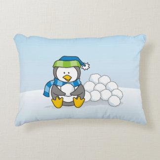 Kleiner Pinguin, der mit Schneebällen sitzt Dekokissen