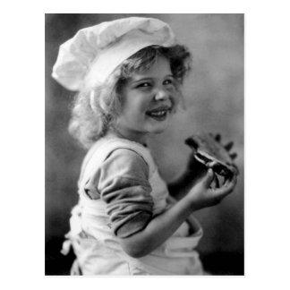 Kleines Bäcker-Mädchen, das Torte isst Postkarte