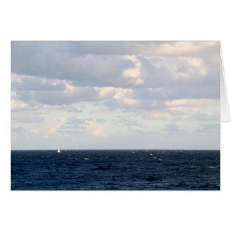 Kleines Segelboot auf einem großen Ozean Mitteilungskarte