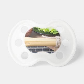 Kopfsalat in einer schwarzen Platte, Teigwaren in Schnuller