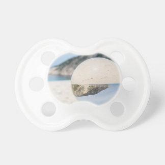 Kristallball auf sandigem griechischem Strand Schnuller