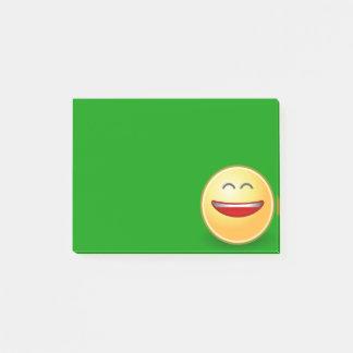 Lächelndes Gesicht auf grüner Post-Itanmerkung Post-it Klebezettel