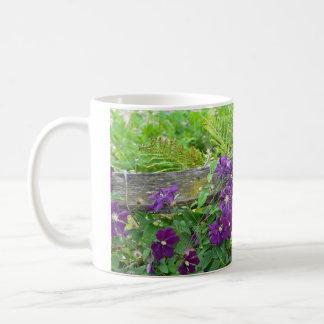 Lila Clematis-Blumen auf hölzernem Zaun Kaffeetasse