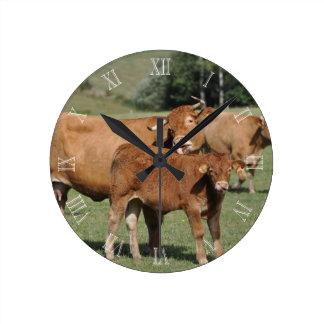 Limousin-Kuh, die ihr Kalb wäscht Runde Wanduhr