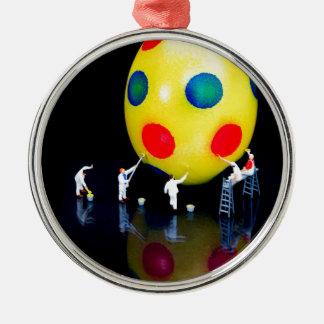 Miniaturfigürchen, die gelbes Osterei malen Silbernes Ornament