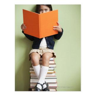 Mischrassemädchen, das auf Stapel Büchern sitzt Postkarte