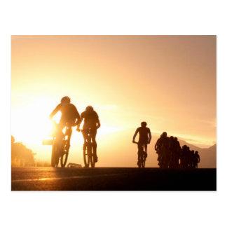 Mountainbike-Reiter machen ihre Weise über der Postkarten