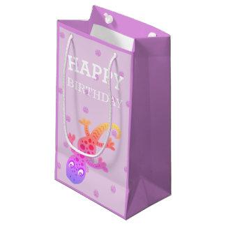 Niedliche kleine Regenbogengecko-Eidechse auf Rosa Kleine Geschenktüte